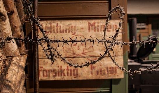Piggtrådgjerde i forgrunnen, tysk skilt i bakgrunnen med advarsel om minefelt i bakgrunnen.