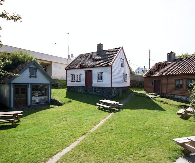 Uteareal mellom husene i Dokken museum. Viser kolonialbutikken, losahuset og stavahuset.