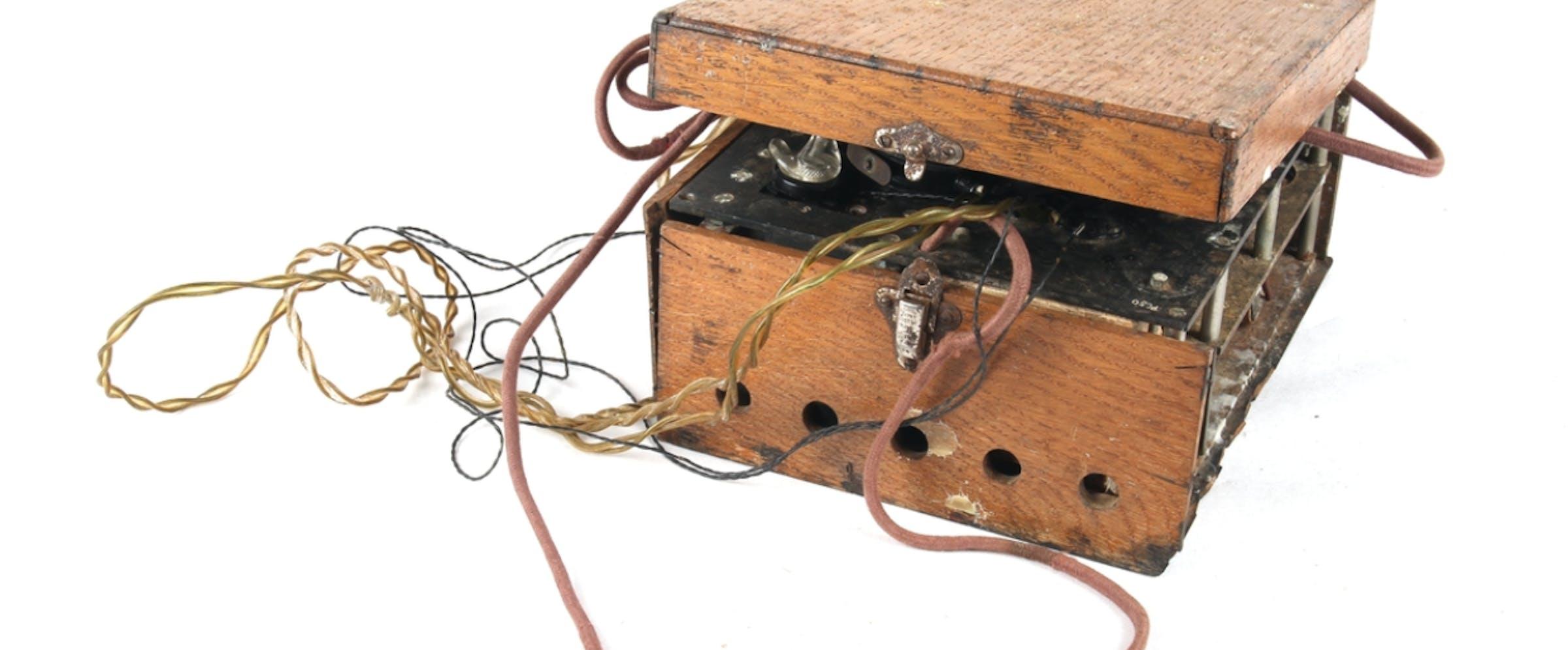 Hjemmelaget radio i treboks, med tilhørende kabler og hodetelefoner.